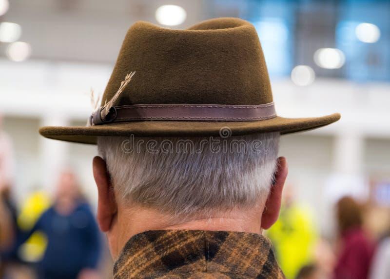 牛仔女装设计 更老的人佩带的牛仔帽画象从后面 免版税库存图片