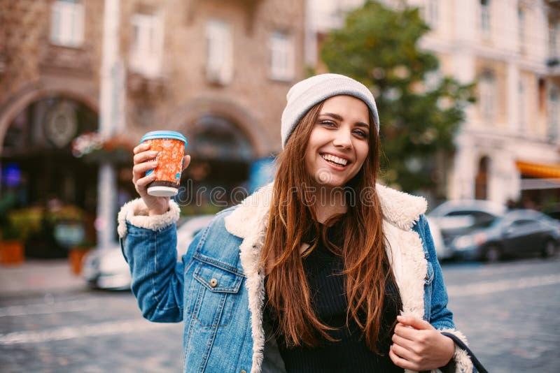 牛仔布外套和被编织的帽子的画象俏丽的女孩走在街道上的 她在白色手套,微笑拿着咖啡进来友好 免版税库存图片