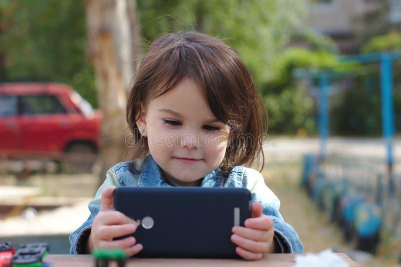 牛仔布夹克的女孩在她的手和神色上举行入智能手机,当在桌上坐操场时 免版税库存照片