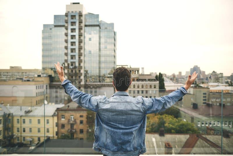 牛仔布夹克的年轻人在大阳台站立 免版税库存照片