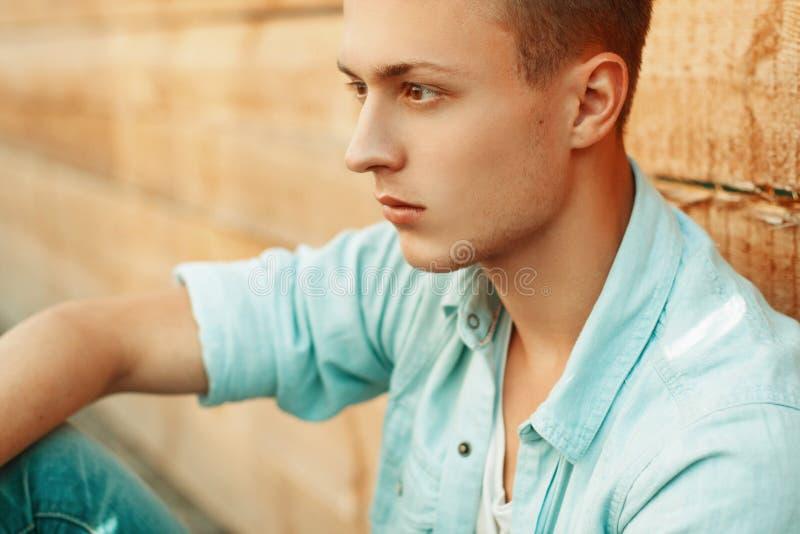 牛仔布的年轻哀伤的人在木墙壁背景穿衣  免版税库存图片