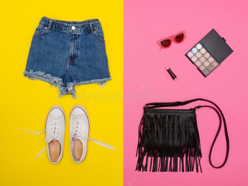 牛仔布短缺,白色运动鞋,黑提包,化妆用品 明亮的黄色和桃红色背景 免版税库存照片