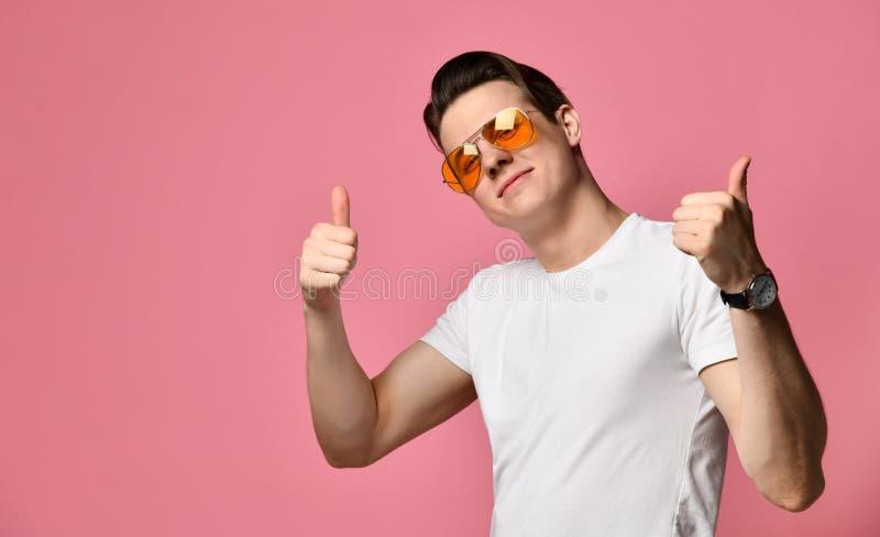 牛仔布短裤和白色T恤的年轻微笑的人,隔绝在桃红色 库存照片