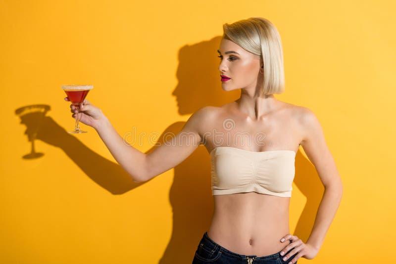 牛仔布短裤的美丽的年轻白肤金发的妇女和上面对负玻璃与鸡尾酒 免版税库存图片