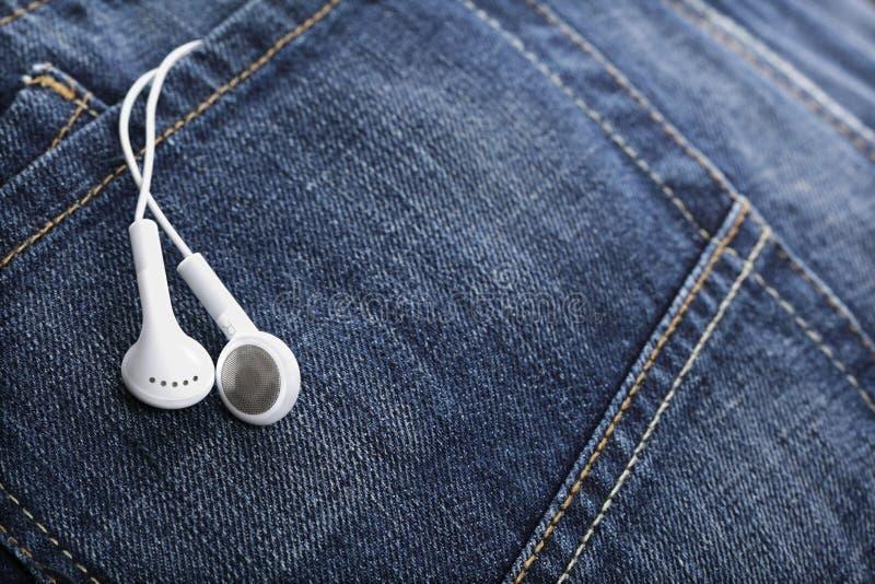 牛仔布耳机牛仔裤装在口袋里白色 图库摄影