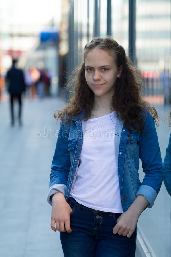 牛仔布衣裳的美丽的青少年的女孩站立倾斜在城市街道上的玻璃大厦 库存照片