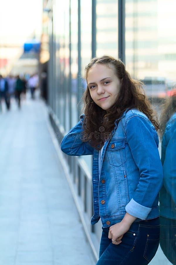 牛仔布衣裳的美丽的青少年的女孩站立倾斜在城市街道上的玻璃大厦 免版税库存图片