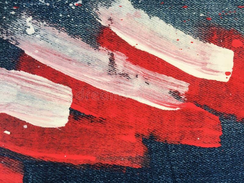 牛仔布,牛仔裤纹理背景 在帆布的抽象油漆纹理 五颜六色的油漆下落在蓝色背景牛仔布的 库存照片