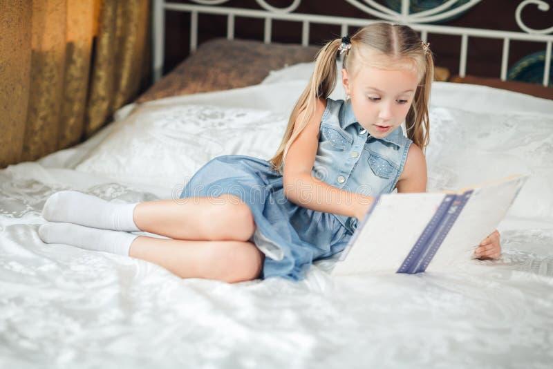 牛仔布sundress看书的逗人喜爱的女孩在床上在家 免版税库存照片