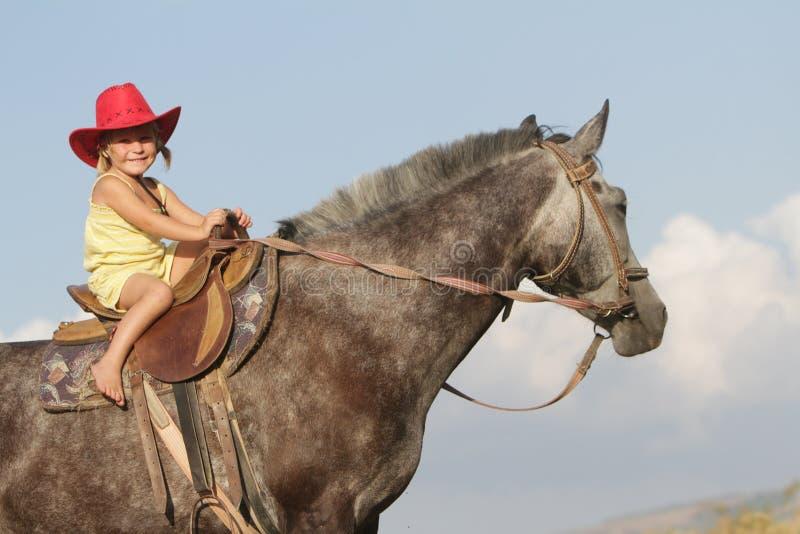 牛仔帽骑乘马的愉快的女孩 库存照片