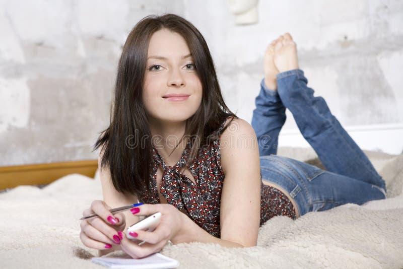 牛仔裤位于的沙发妇女 免版税库存照片