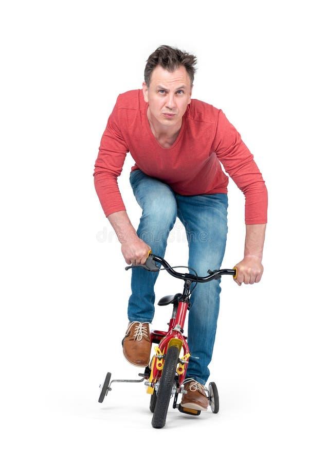 牛仔裤和一件红色T恤杉的滑稽的人在小孩子的自行车滚动 o r 免版税库存照片