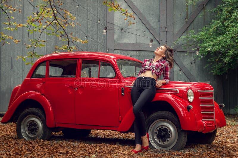 牛仔裤和格子花呢上衣的画报女孩在俄国红色减速火箭的汽车倾斜 库存照片