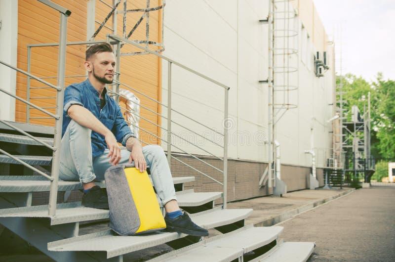 牛仔裤和牛仔布衬衣的年轻人坐工厂厂房台阶在他的背包旁边,当等待时 免版税图库摄影