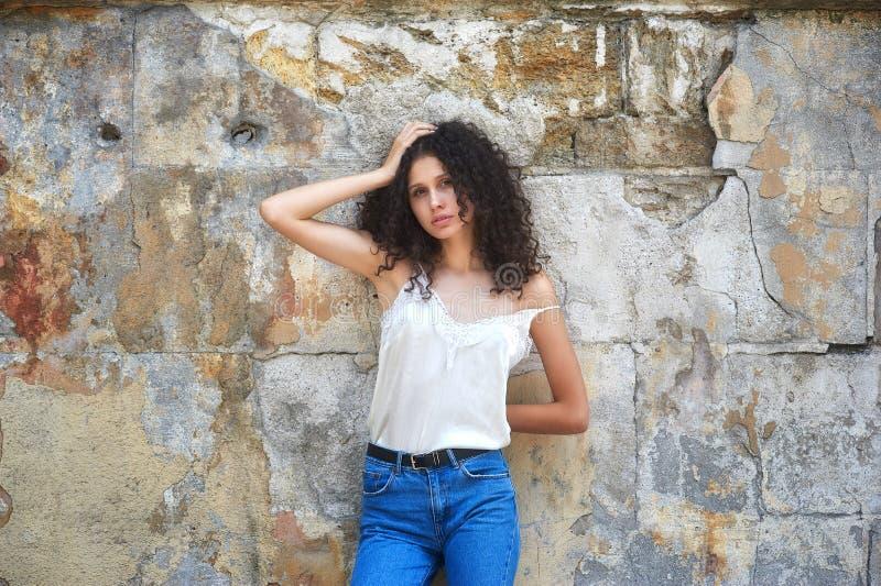 牛仔裤和白色女衬衫的年轻美女在老城市街道上 库存照片