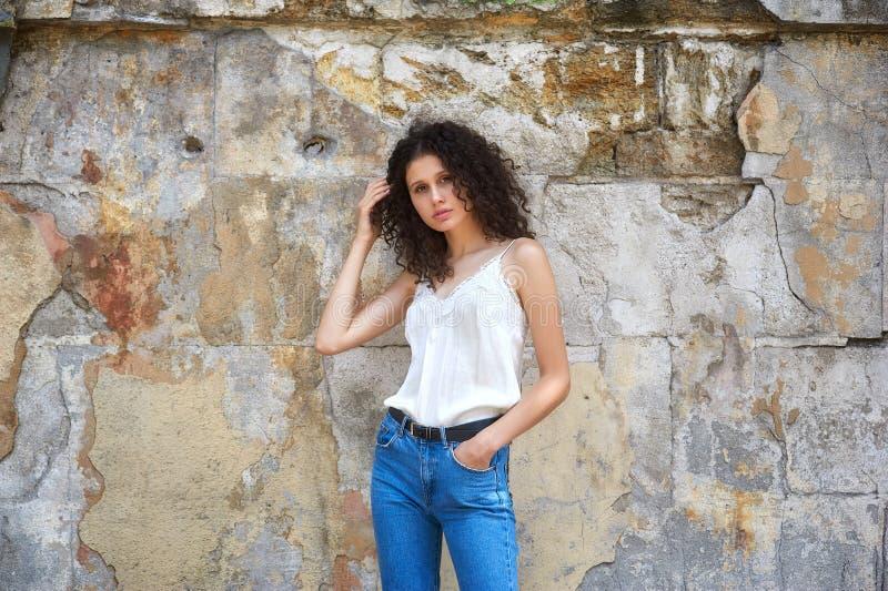 牛仔裤和白色女衬衫的年轻美女在老城市街道上 免版税库存照片