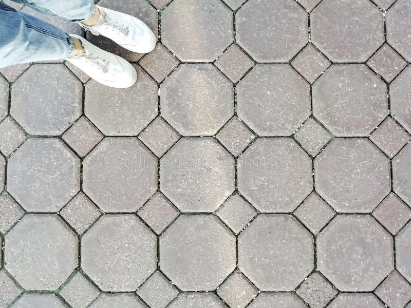 牛仔裤和白色运动鞋的腿女孩在边路的瓦片的背景中 图库摄影