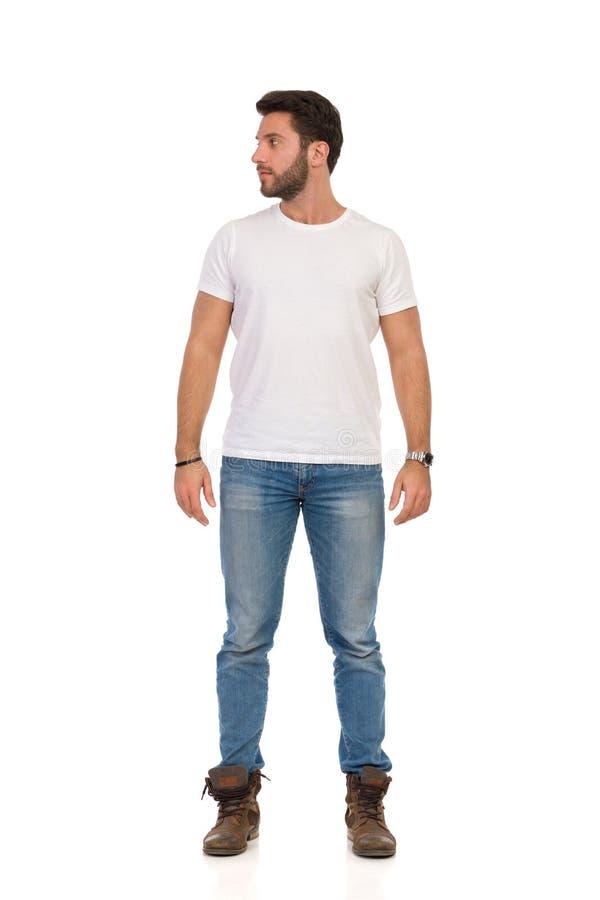 牛仔裤和白色T恤的严肃的人是站立和看  o 免版税库存图片