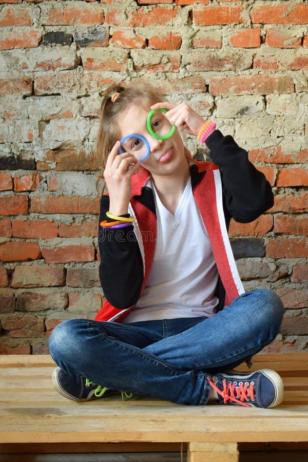 牛仔裤和白色T恤的少女坐地板和微笑 一个宜人的友好的愉快的少年的概念画象 库存图片