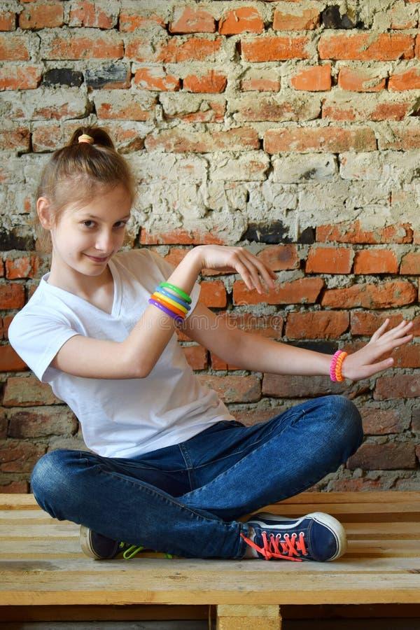 牛仔裤和白色T恤的少女坐地板和舞蹈 一个宜人的友好的愉快的少年的概念画象 免版税图库摄影