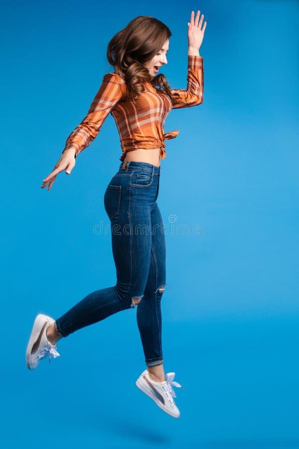 牛仔裤和被检查的衬衣和运动鞋跳跃的时髦少女 免版税图库摄影