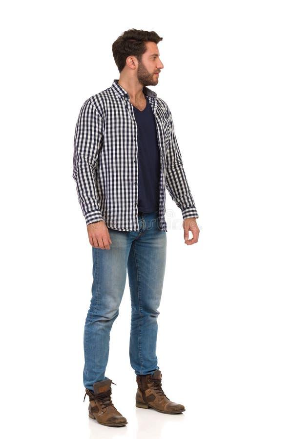 牛仔裤和被解扣的伐木工人衬衣的严肃的Handsme人看  库存图片