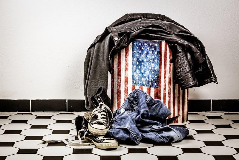 牛仔裤和说谎在地板上的体育鞋子 免版税库存图片