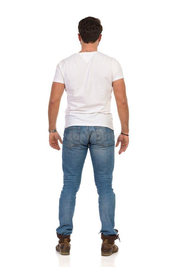 牛仔裤和WhiteT衬衣的年轻人站立放松的,背面图 免版税库存照片