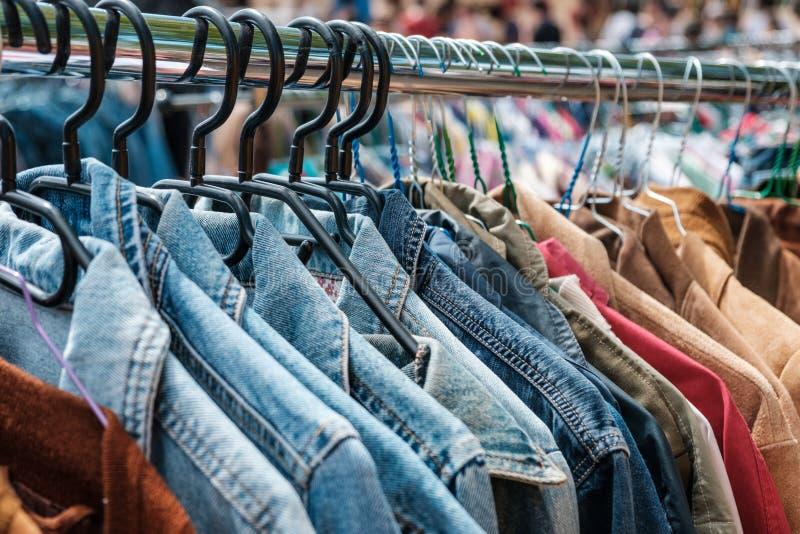牛仔裤夹克和减速火箭的衬衣在二手货市场/蚤3月上 免版税库存图片