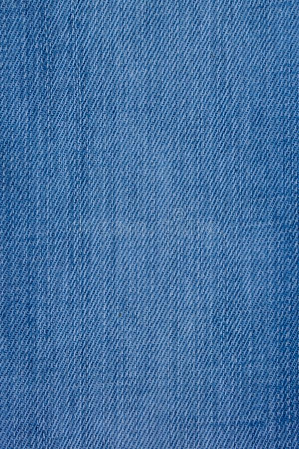 牛仔裤物质与一种概略的纹理蓝色颜色 库存照片