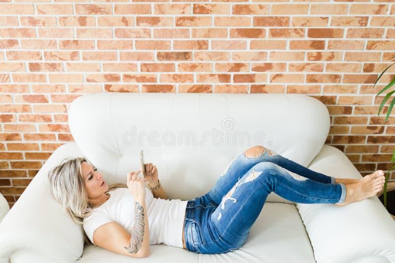 牛仔裤的年轻女人使用说谎在白色沙发的智能手机 免版税库存图片