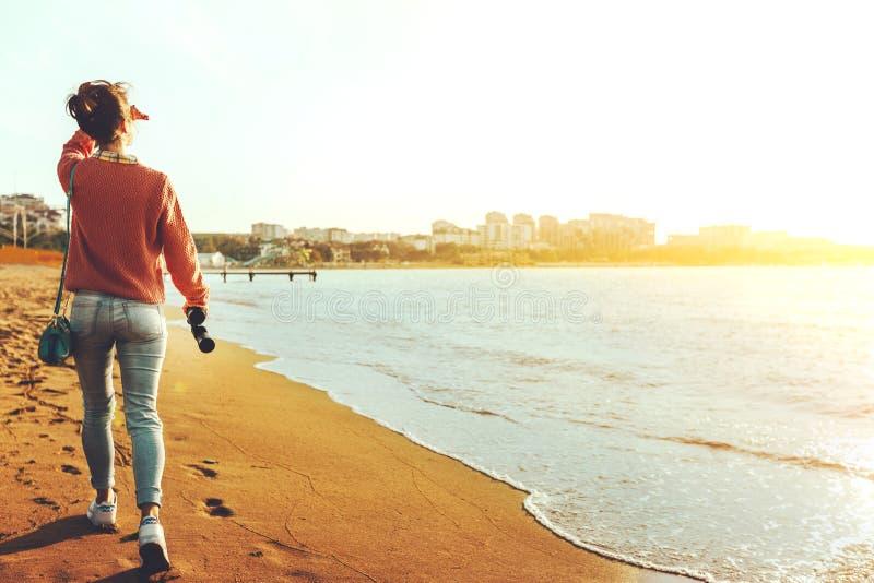 牛仔裤的无法认出的远足者女孩沿与双筒望远镜的海滨,背面图走 侦察员旅行癖假日概念 免版税库存照片