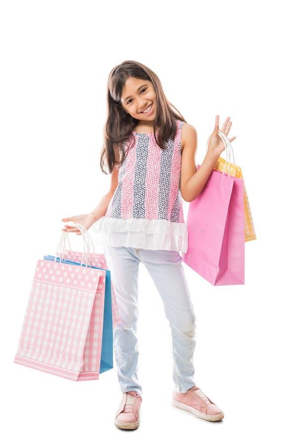 牛仔裤的甜拿着五颜六色的纸购物袋的女孩和上面 免版税图库摄影