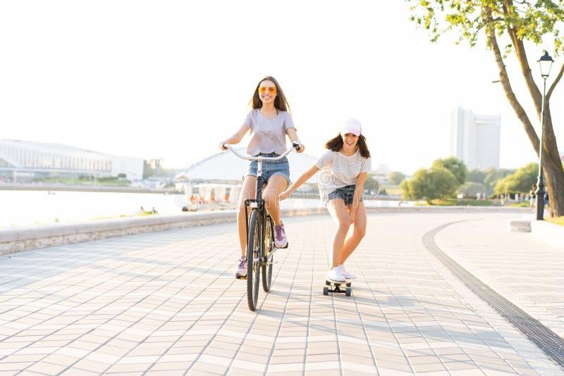 牛仔裤的逗人喜爱的笑的少妇在拉扯女孩的自行车短缺举行,当曾经滑板时 免版税图库摄影