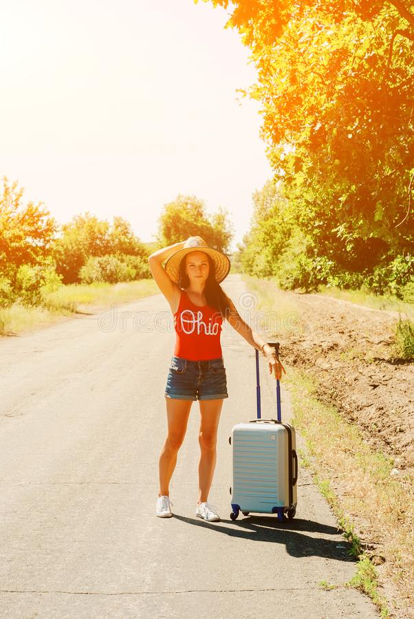 牛仔裤短裤和帽子的性感的妇女 国家(地区)女孩偏僻的路手提箱 库存图片