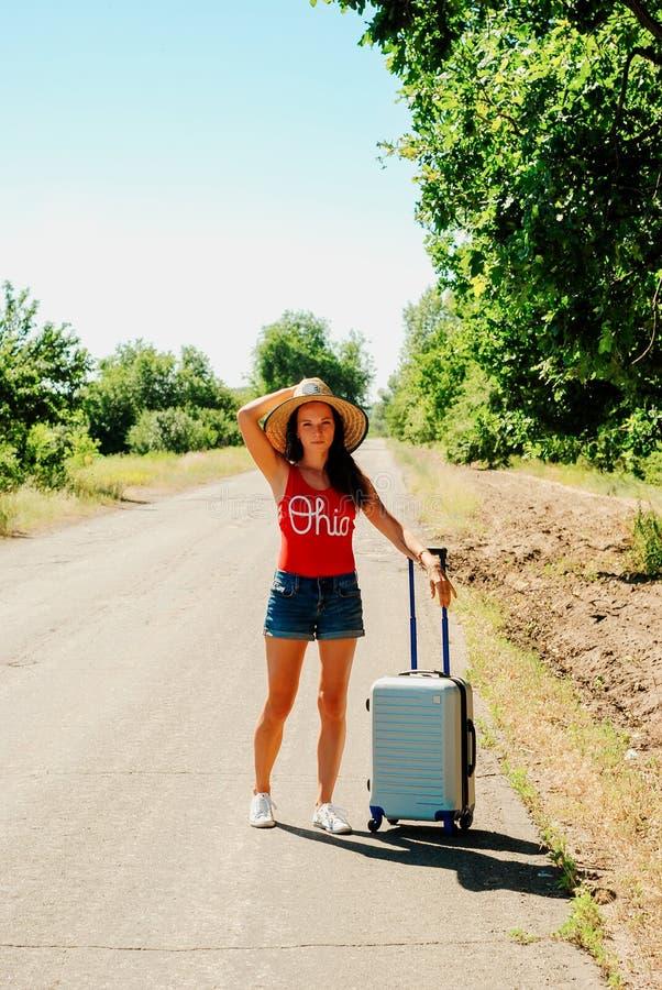 牛仔裤短裤和帽子的性感的妇女 国家(地区)女孩偏僻的路手提箱 免版税库存照片