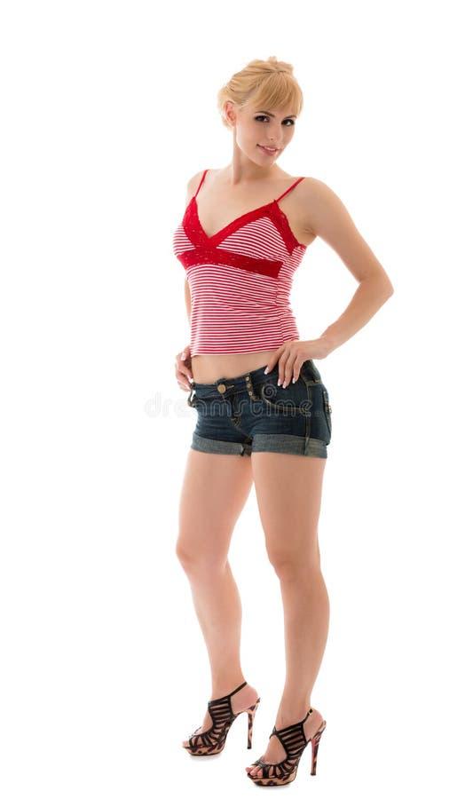 牛仔裤短裤和红顶的性女孩 免版税库存照片