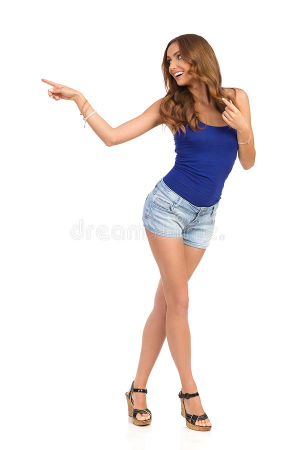 牛仔裤短裤的无忧无虑的妇女是指向和看  免版税库存照片