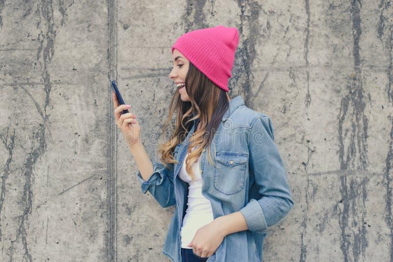 牛仔裤衣物和桃红色帽子的笑的愉快的激动的女孩使用智能手机和通信的前面照相机通过实习生 免版税库存图片