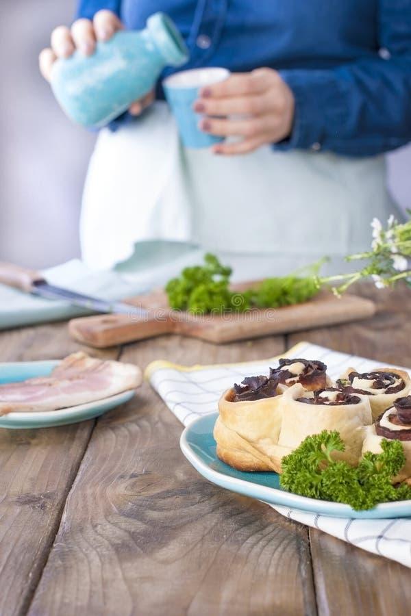 牛仔裤衣裳的一个女孩准备烟肉和面团午餐,用新鲜的草本 背景棕色木 蓝色cet Kramic盘  免版税库存图片