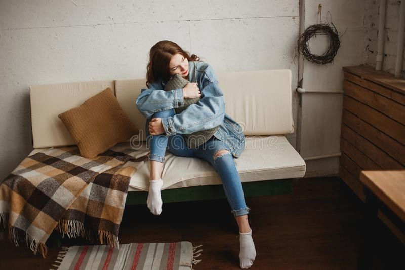 牛仔裤衣裳的逗人喜爱的年轻女人获得乐趣在沙发 库存图片