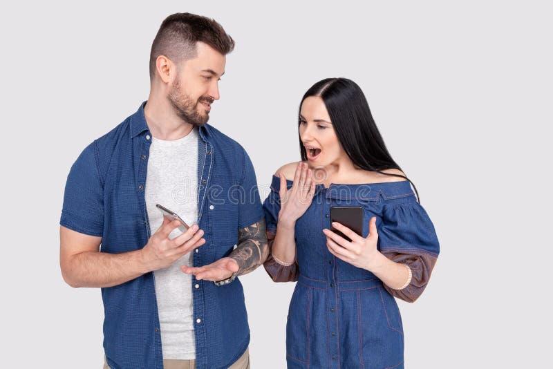 牛仔裤衬衣显示某事在手机的藏品智能手机的年轻不剃须的人对她的妻子 惊奇的年轻女性看 免版税图库摄影