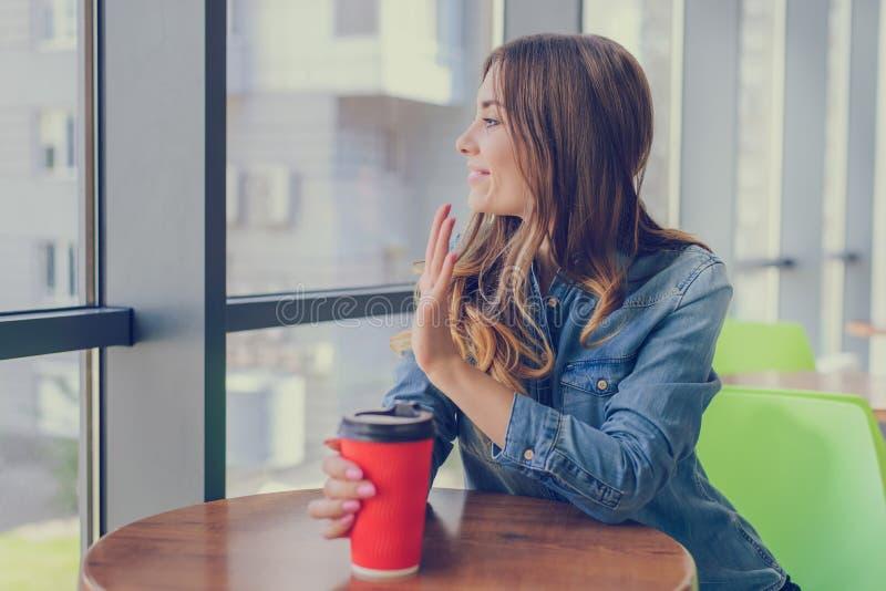 牛仔裤衬衣饮用的咖啡的微笑的女孩,坐在咖啡馆和挥动对她的朋友 外带的商店多哥咖啡 等待 库存照片