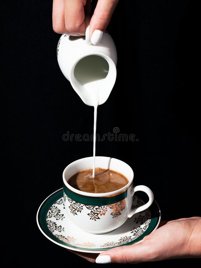 牛奶倒在黑coffe 库存图片