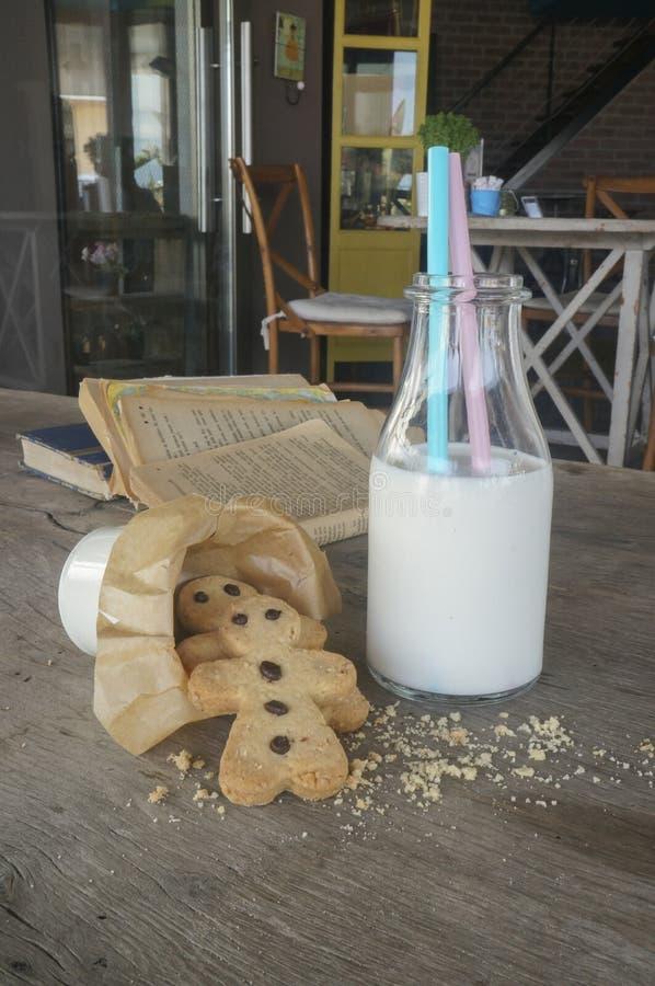 牛奶和曲奇饼在土气木桌上 免版税库存照片