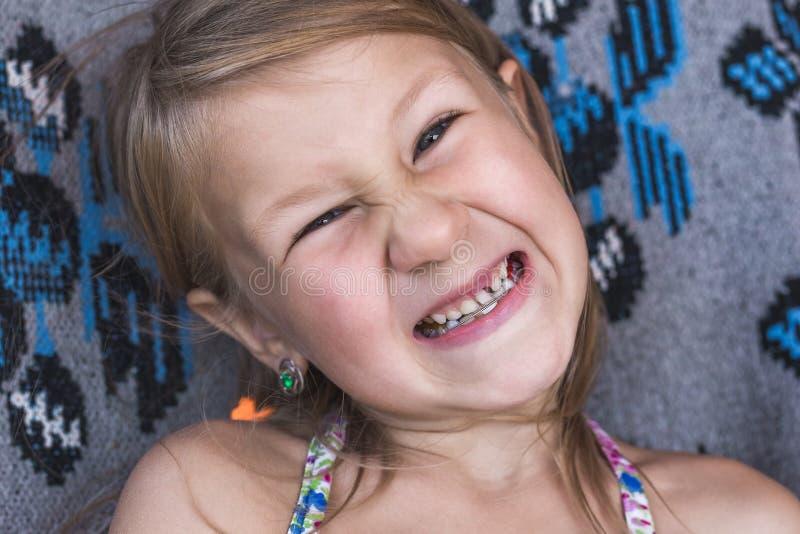 牛奶店牙落在孩子外面 女孩摆动活动的牙齿 图库摄影
