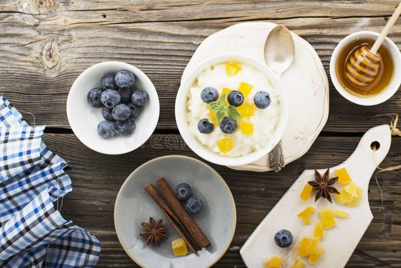 牛奶店自创大米布丁用蓝莓和糖煮的梨在木背景 概念的健康季节性 库存照片