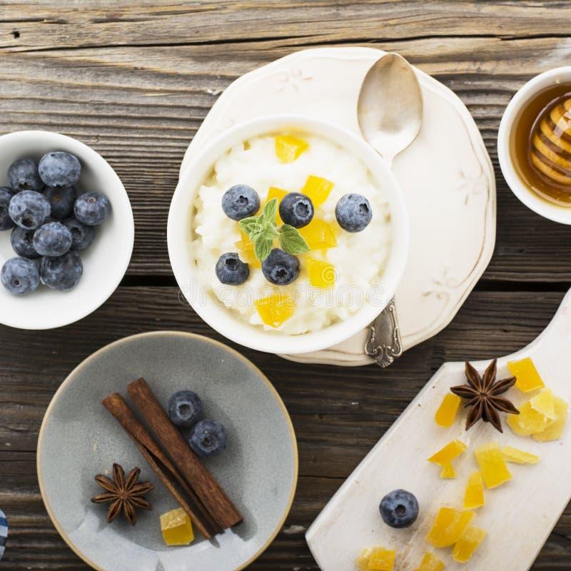 牛奶店自创大米布丁用蓝莓和糖煮的梨在木背景 概念的健康季节性 免版税库存照片