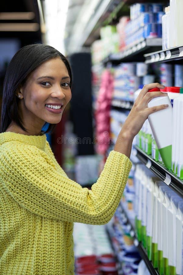 从牛奶店部分的妇女买的牛奶 免版税库存图片