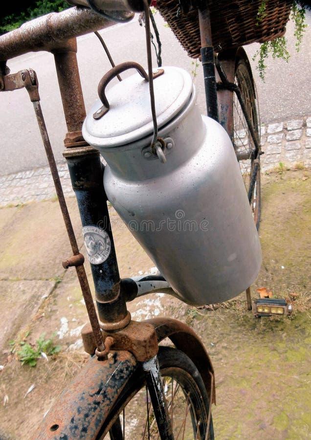 牛奶罐头锡在生锈的自行车垂悬 库存照片